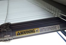 This file photo shows a warning label of strangulation risks from mini blind cords in Washington. According to a study released this month, children's injuries and deaths from window blinds have not stalled despite decades of safety concerns. (AP Photo/Jacquelyn Martin)
