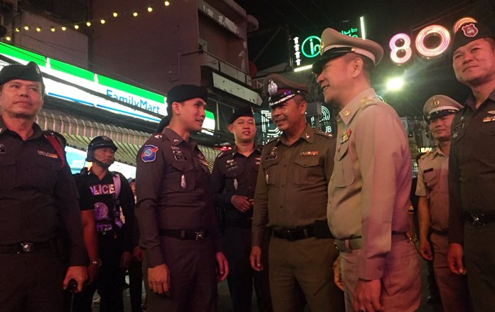 District Chief Naris Niramaiwong and Police Chief Pol. Col. Apichai Kroppech walk the nightlife strip with administrators and officers on Christmas night.