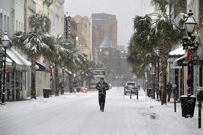 A person walks in the snow on King Street in Charleston, S.C., Wednesday, Jan. 3, 2018. A brutal winter storm smacked the coastal Southeast with a rare blast of snow and ice, hitting parts of Florida, Georgia and South Carolina with their heaviest snowfall in nearly three decades. (Matthew Fortner/The Post And Courier via AP)