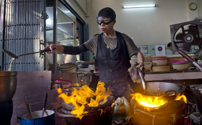 """Thai cook Supinya Jansuta, 72, better known as """"Jay Fai,"""" wearing goggles, cooks with two flaming woks at her eatery in Bangkok. After spending more than three decades cooking in an unassuming outdoor kitchen, Jay Fay has been propelled to international culinary stardom by having her restaurant awarded a Michelin star. (AP Photo/Gemunu Amarasinghe)"""