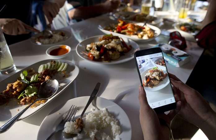 """A customer takes photos of food cooked by Thai cook Supinya Jansuta, 72, better known as """"Jay Fai,"""" at her eatery in Bangkok. (AP Photo/Gemunu Amarasinghe)"""