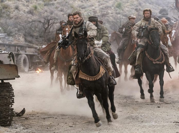 """This image shows Chris Hemsworth (center) in a scene from """"12 Strong."""" (David James/Warner Bros. Entertainment via AP)"""