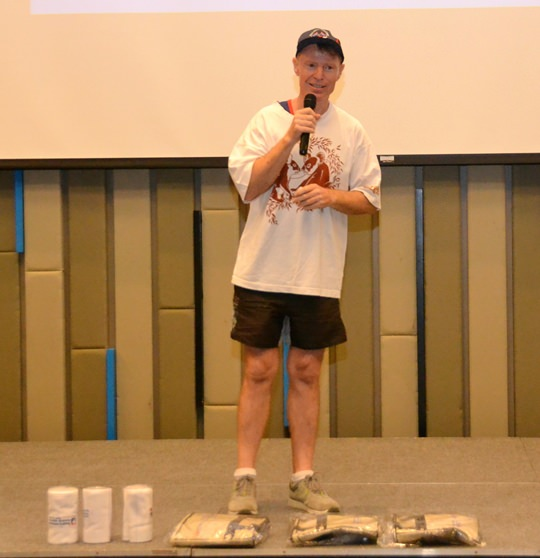 To get things started for learning to be an Aussie for a day, Ren (Lubra Lips) Lexander explains how a little contest between tables involving who can give the Aussie sports call the loudest will win some of the prizes shown at his feet.