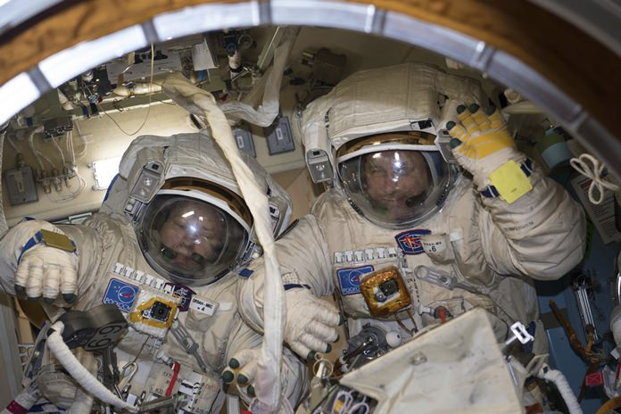 This Jan. 31, 2018 photo made available by NASA shows cosmonauts Alexander Misurkin, left, and Anton Shkaplerov in their Russian Orlan spacesuits during a fit check inside the International Space Station. On Friday, Feb. 2, 2018, the two removed an old electronics box as part of an antenna upgrade at the ISS, then tossed it overboard as a piece of junk. (NASA via AP)