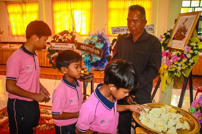Children under the care of HHN Foundation Thailand present sandalwood flowers to their senior member who died.