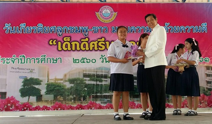 """Banglamung School director Wisanu Pasomsap presents """"outstanding student"""" awards to deserving kids."""