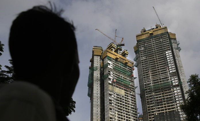 In this Aug. 8, 2017 photo, a man looks at under construction building named Trump Tower in Mumbai, India. The eldest son of President Donald Trump, Donald Trump Jr.is expected to be in India's business capital, on Thursday to quaff champagne with the city's elite at a reception hosted by the Lodha Group, the real estate company that is building the golden-hued Trump Tower. (AP Photo/Rafiq Maqbool)