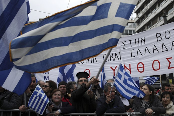 A Greek Orthodox priest waves a flag of his country during a rally in Athens, Sunday, Feb. 4. (AP Photo/Petros Giannakouris)