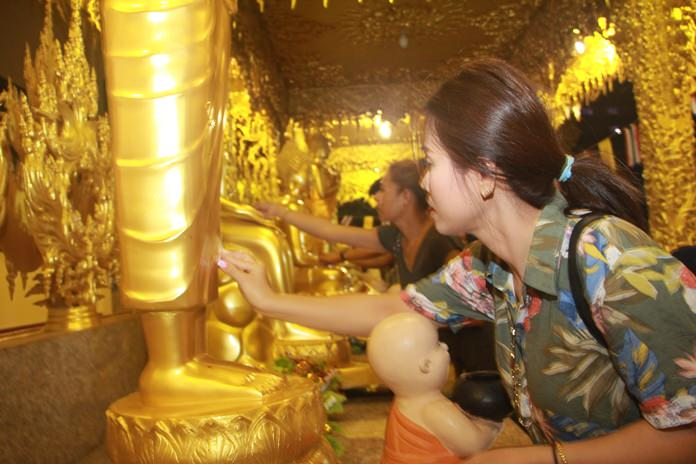 Families join in to paste gold leaf on Bhuddha images as a sign of devotion.