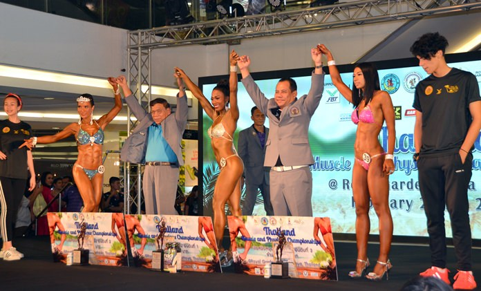 Female competitors pose on stage with tournament officials from the Body Building and Fitness Association of Thailand.