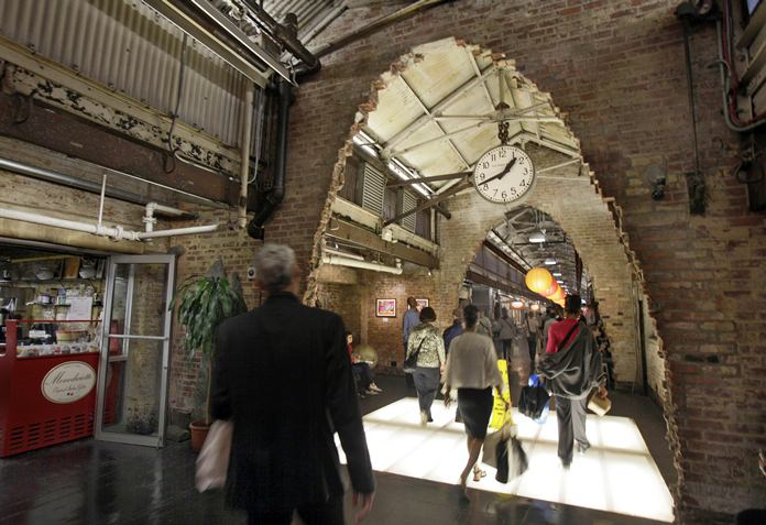 Visitors walk through archways carved out of the brick walls at New York's landmark Chelsea Market building in the Meatpacking District. Google, which has an office building across the street on Ninth Avenue, is reportedly close to reaching a $2.4 billion deal to add the Chelsea Market building. (AP Photo/Richard Drew, File)