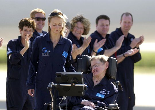 Astrophysicist Stephen Hawking is assisted off the tarmac at the Kennedy Space Center by his caregiver, Monica Guy, as he is applauded by members of the flight crew after completing a zero-gravity flight, Thursday, April 26, 2007. (AP Photo/Peter Cosgrove, File)