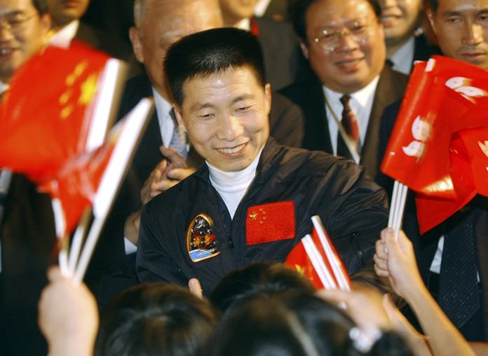 In this Oct. 31, 2003, file photo, school children wave Chinese and Hong Kong flags as they welcome China's first astronaut Yang Liwei, center. China says it plans to begin recruiting civilian astronauts for its military-backed space program. (AP Photo/Anat Givon, File)
