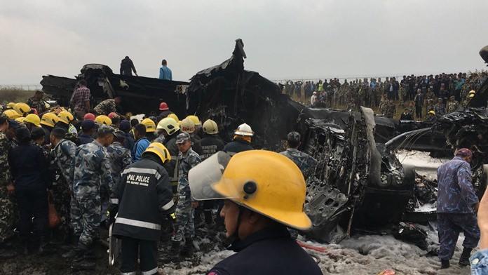 Nepalese rescuers stand near a passenger plane from Bangladesh that crashed at the airport in Kathmandu, Nepal, Monday, March 12. (AP Photo/Niranjan Shreshta)