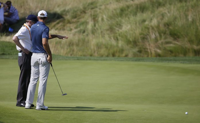 In this June 19, 2016, file photo, Dustin Johnson, right, talks to a rules official on the fifth green during the final round of the U.S. Open golf tournament at Oakmont Country Club in Oakmont, Pa. (AP Photo/John Minchillo)