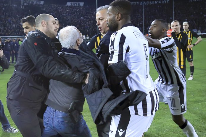 PAOK owner, businessman Ivan Savvidis, second from left, approaches AEK Athens' Manager Operation Department Vassilis Dimitriadis, center, as his bodyguard and PAOK's players Fernando Varela, second from right, and Djalma Campos, right, try to stop him during a Greek League soccer match between PAOK and AEK Athens in the northern Greek city of Thessaloniki, Sunday, March 11. (InTime Sports via AP)