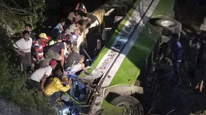 In this Tuesday, March 20, photo rescuers and volunteers try to help trapped passengers escape from the wreckage of the passenger bus after it careened off a road and fell into a ravine at Sablayan township, Mindoro Occidental province in central Philippines. (PDRRMO, Mindoro Occidental via AP)