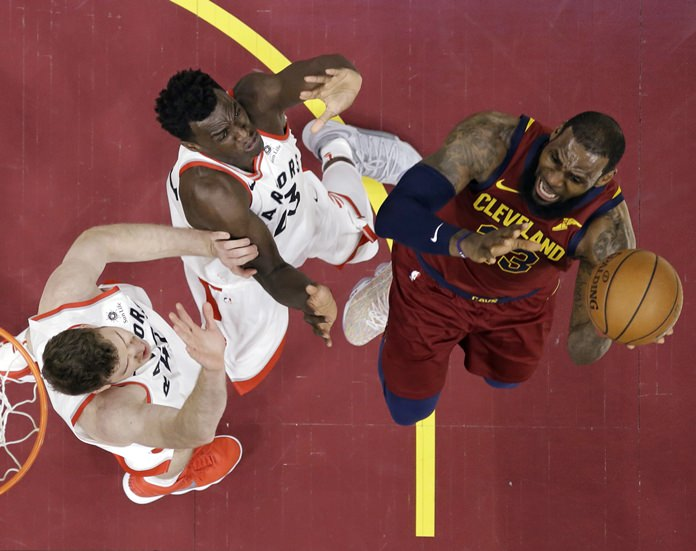Toronto Raptors' Jakob Poeltl, left, and Pascal Siakam defend against Cleveland Cavaliers' LeBron James during the first half of an NBA basketball game Wednesday, March 21, in Cleveland. (AP Photo/Tony Dejak)