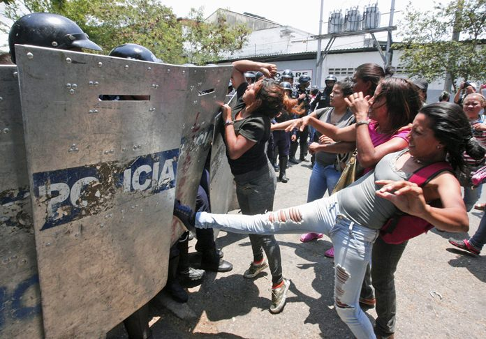 A woman kicks at a riot police shield as relatives of prisoners wait to hear news about their family members imprisoned at a police station where a fire broke out, in Valencia, Venezuela, Wednesday, March 28. (AP Photo/Juan Carlos Hernandez)