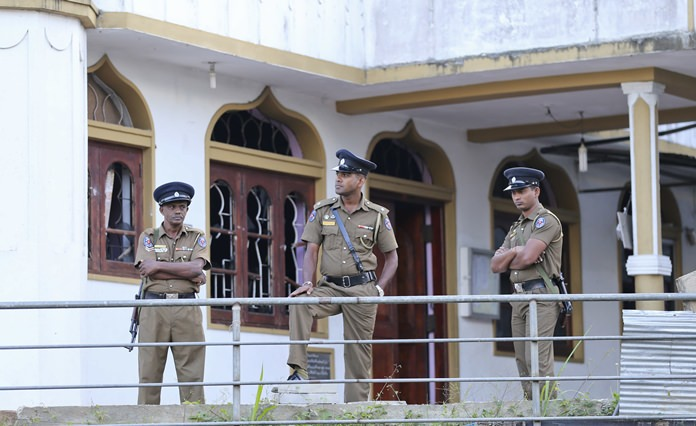 Sri Lankan police officers stand outside a vandalized Mosque in Poojapitiya, in central Sri Lanka, Wednesday, March 7. (AP Photo/Rukmal Gamage)