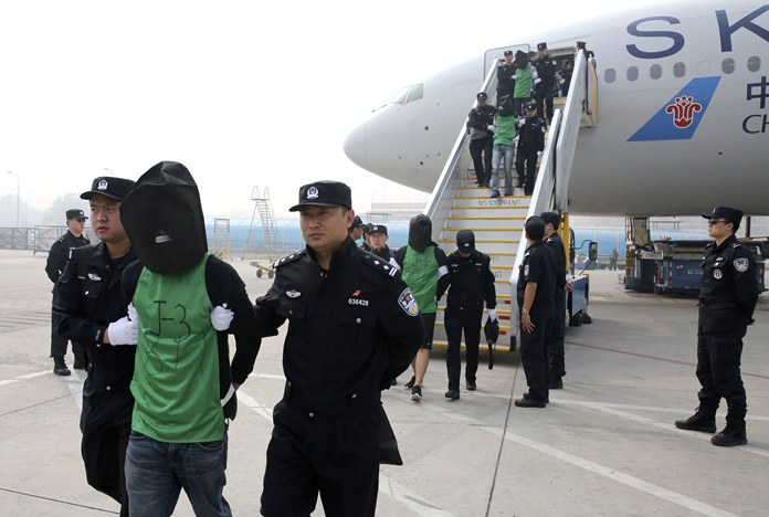 In this April 13, 2016, file photo, Chinese and Taiwanese suspects involved in wire fraud are escorted off a plane upon arriving in Beijing. (Yin Gang/Xinhua via AP)