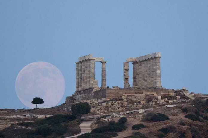 In this June 20, 2016 file photo, the full moon rises near the ancient marble Temple of Poseidon at Cape Sounion, southeast of Athens. (AP Photo/Petros Giannakouris)