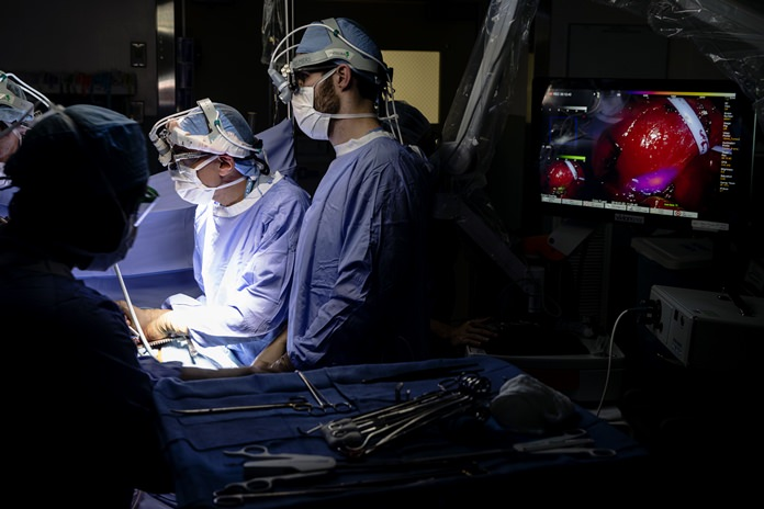 Dr. Sunil Singhal, second from right, directs a special camera to view a tumor in his patient made visible with a fluorescent dye, seen at monitor on right, at the Hospital of the University of Pennsylvania in Philadelphia, Tuesday, Jan. 23, 2018. Researchers are testing fluorescent dyes that make cancer cells glow to make them easier for surgeons to find, giving patients a better shot at survival. (AP Photo/Matt Rourke)