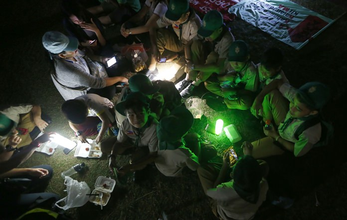 Filipino boy scouts use the light of their cellphones as they observe Earth Hour. (AP Photo/Bullit Marquez)