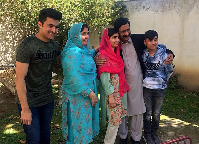 Pakistan's Nobel Peace Prize winner Malala Yousafzai, center, poses for a photograph with her family members at her native home during a visit to Mingora, the main town of Pakistan Swat Valley, Saturday, March 31, 2018. Yousafzai arrived in her hometown for the first time since a Taliban militant shot her there in 2012 for advocating girls' education. (AP Photo/Abdullah Sherin)