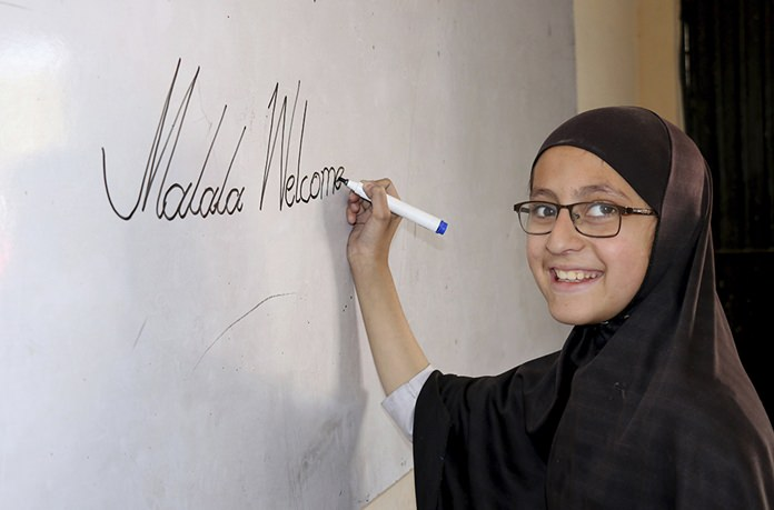 A Pakistani student of the school of Nobel Peace Prize winner Malala Yousafzai writes on a board in her hometown of Swat Valley in Pakistan. (AP Photo/Naveed Ali)