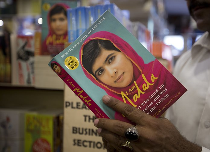A Pakistani customer looks over Nobel Peace Prize winner Malala Yousafzai's book at a book store in Islamabad, Pakistan. (AP Photo/B.K. Bangash)