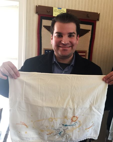 Adam Sackowitz holds up an embroidered pillowcase with celestial bodies on it that belonged to the late John Glenn (Courtesy of Adam Sackowitz via AP)
