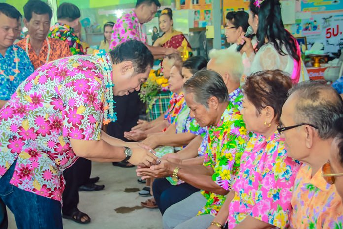 Sonthaya Kunplome pours lustral water on his elders in Soi Khopai.