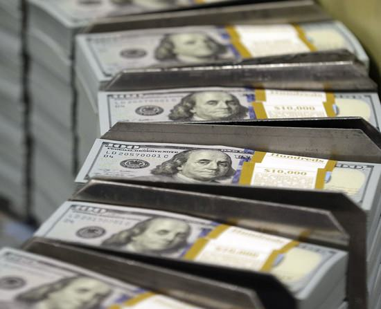 Cut stacks of $100 bills make their way down the line at the Bureau of Engraving and Printing Western Currency Facility in Fort Worth, Texas. Middle-aged Americans who experienced a sudden, large economic blow were more likely to die during the following years than those who didn't. (AP Photo/LM Otero)