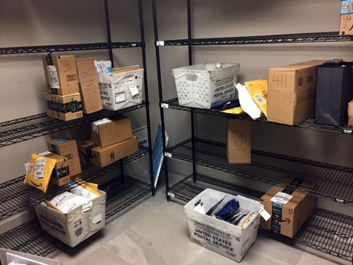 "In this April 13, 2018, photo, packages from Internet retailers are delivered with the U.S. Mail in an apartment building mail room in Washington. Clicking ""checkout"" on an online purchase could cost more after a Supreme Court case being argued. (AP Photo/Jessica Gresko)"