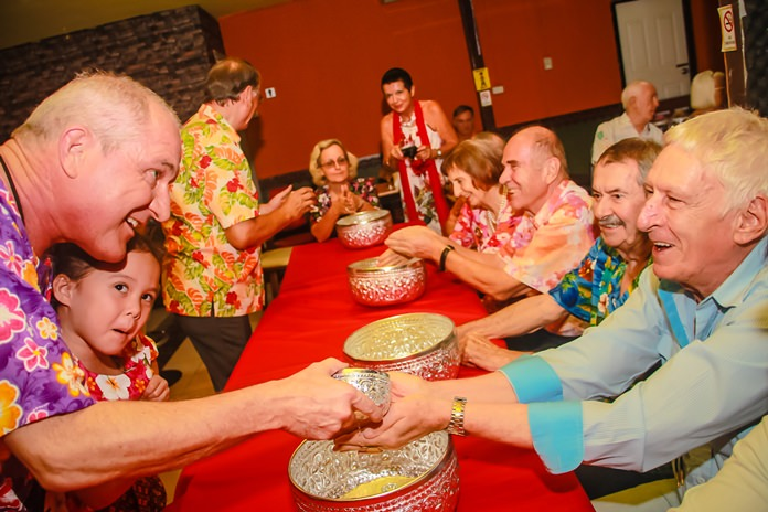 PP Dr Olivier Meyer together with one of his lovely daughters pours lustral water on the hands of Peter Schlegel, President of the Rotary Club of Phoenix Pattaya.