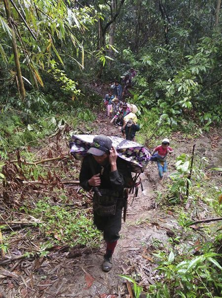 In this photo provided by Labram Hkun Awng, Kachin civilians displaced by fighting between the Myanmar military and Kachin guerrillas walk through jungle close to Tanai, northern Kachin state, Myanmar Thursday, April 19, 2018. (Labram Hkun Awng via AP Photo)