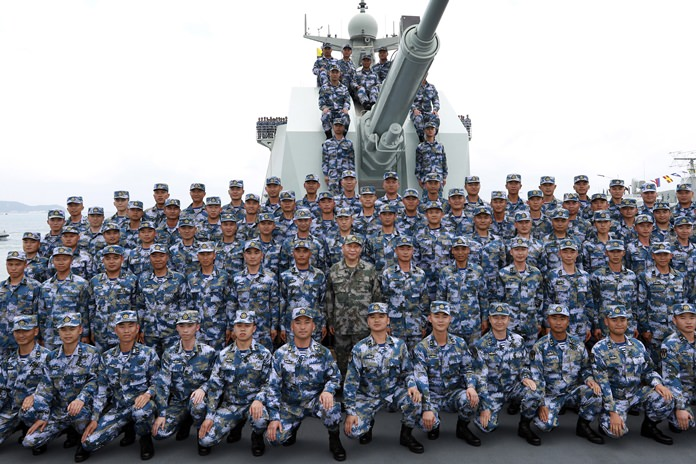In this April 12, 2018, Chinese President Xi Jinping, center in green military uniform, poses with soldiers on a navy ship after he reviewed the Chinese People's Liberation Army (PLA) Navy fleet in the South China Sea. (Li Gang/Xinhua via AP)