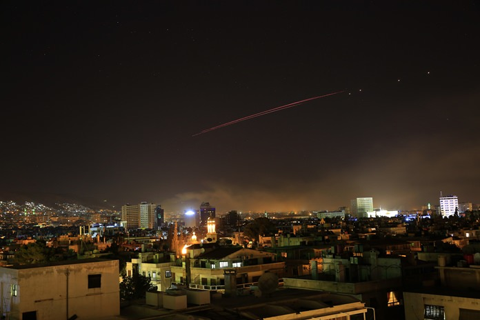 Explosions and anti-aircraft fire light up the skies over Damascus, the Syrian capital, as the U.S. launches an attack on Syria, early Saturday, April 14. (AP Photo/Hassan Ammar)