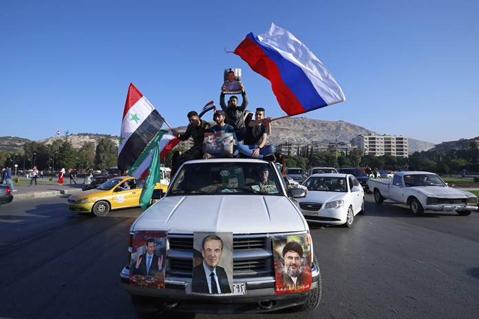 Syrian government supporters wave Syrian, Iranian and Russian flags as they chant slogans against U.S. President Trump in Damascus, Syria, Saturday, April 14. (AP Photo/Hassan Ammar)