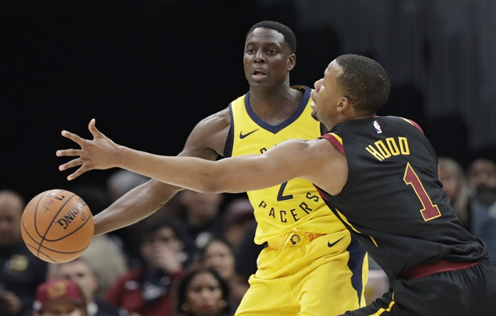Indiana Pacers' Darren Collison (2) passes around Cleveland Cavaliers' Rodney Hood (1) in the first half of Game 1 of an NBA basketball first-round playoff series, Sunday, April 15, in Cleveland. (AP Photo/Tony Dejak)