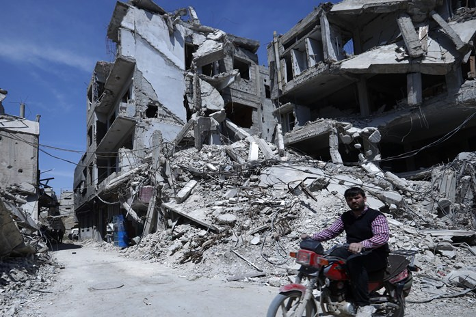 A man rides past destroyed buildings in the town of Douma, the site of a suspected chemical weapons attack, near Damascus, Syria, Monday, April 16. (AP Photo/Hassan Ammar)