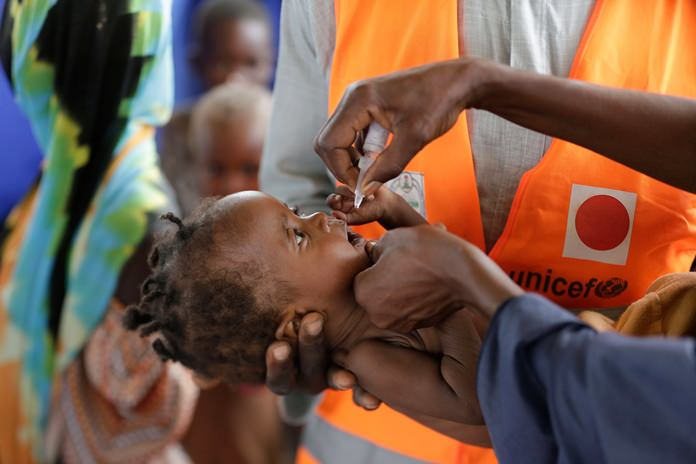 In this Saturday, Aug. 27, 2016, file photo, a health official from the United Nations International Children's Emergency Fund (UNICEF) administers a polio vaccine to a child at a camp for people displaced by Islamist extremists, in Maiduguri, Nigeria. (AP Photo/Sunday Alamba)
