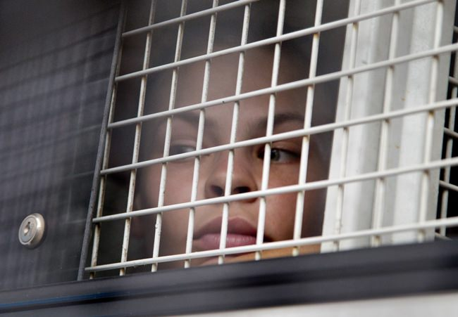 Anastasia Vashukevich sits inside a prison transport vehicle outside a courthouse in Pattaya, Tuesday, April 17. (AP Photo/Gemunu Amarasinghe)