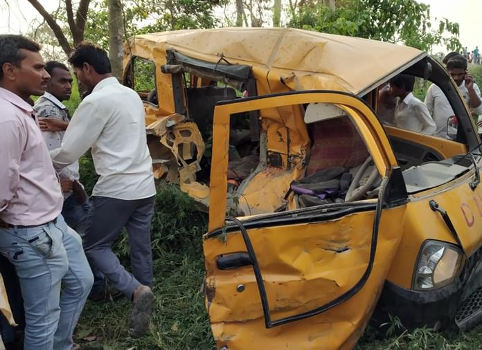 Indian men inspect a school van that was hit by a train at an ungated railroad crossing, near Kushinagar, in the northern Indian state of Uttar Pradesh, Thursday, April 26. (AP Photo)