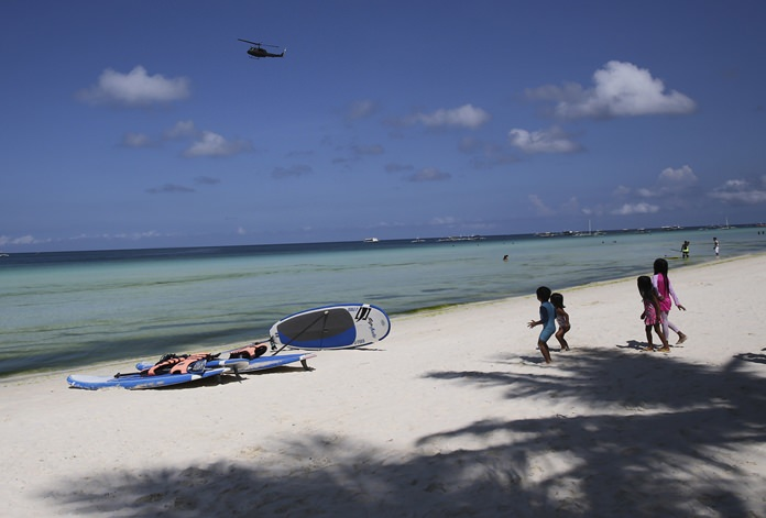 Children watch as a military helicopter passes by the country's most famous beach resort island Wednesday, April 25, 2018, a day before the government implements its temporary closure. (AP Photo/Aaron Favila)