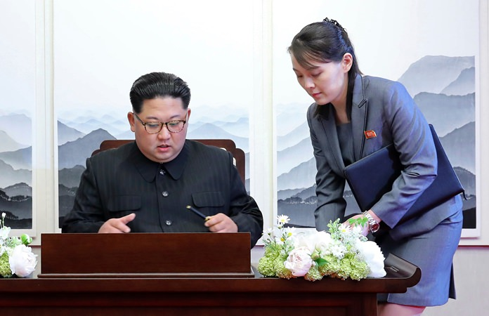 North Korean leader Kim Jong Un signs a guestbook next to his sister Kim Yo Jong, right, inside the Peace House. (Korea Summit Press Pool via AP, File)