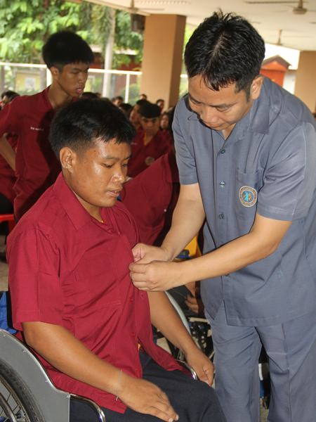 Teachers help the students into their new uniforms.