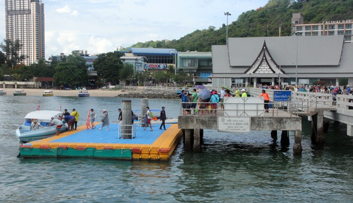 Tourists make their way down from the pier to the pontoon to board a speedboat.