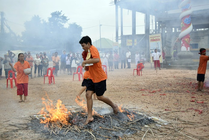 A devotee walks barefoot over a bed of hot embers as he carries an image of Chao Mae Lim Kor Niew during the annual festival to honor the goddess of fire and water. It is believed that the ritual purifies the participants, proves their faith and fulfills their vows and helps ward off evil spirits while praying for luck and good fortune.